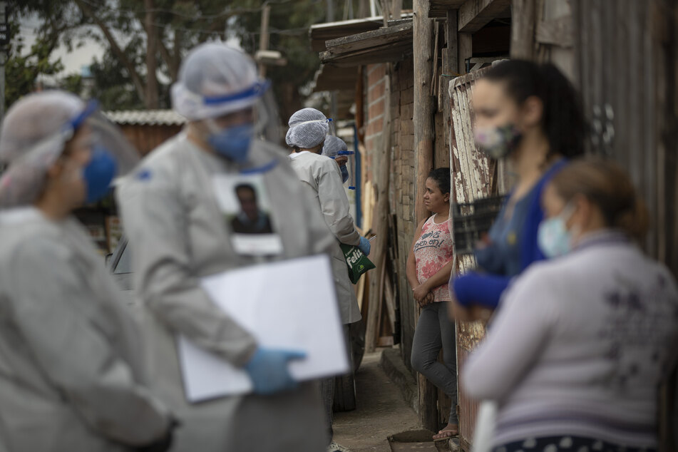 Mitglieder von Ärzte ohne Grenzen sprechen mit Anwohnern in einem besetzten Gebiet, um die Ausbreitung des Covid-19 zu verhindern.