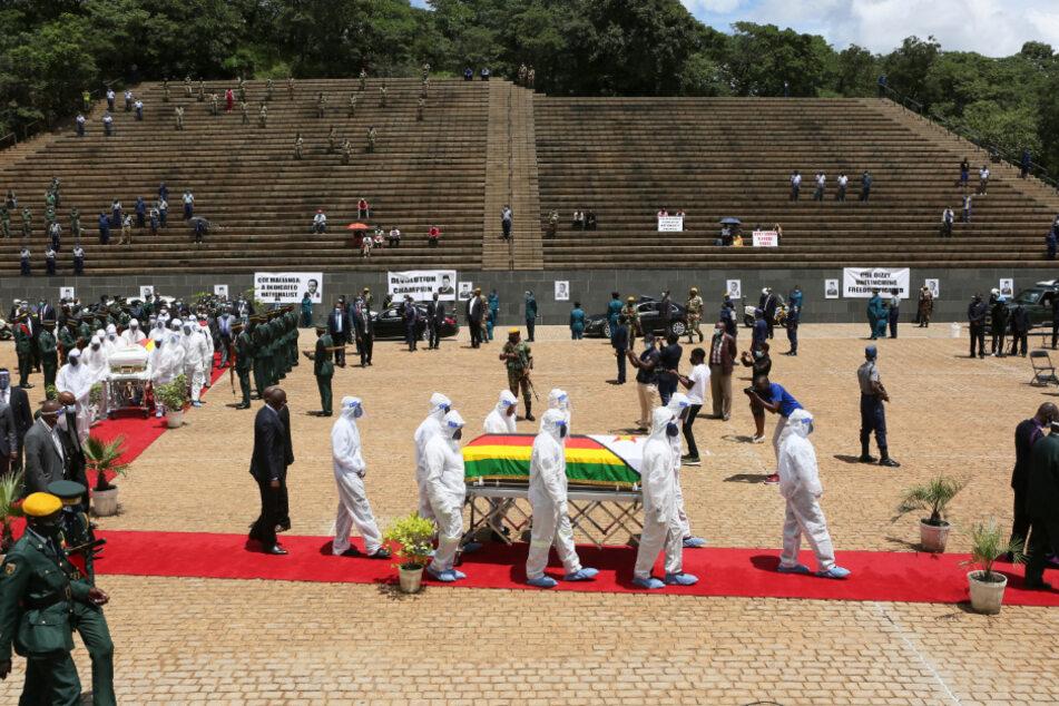 """Simbabwe, Harare: Menschen in Schutzkleidung tragen den Sarg der an Corona verstorbenen Ministerin Dr. Ellen Gwaradzimba über die Grabstätte """"Heroes Acre""""."""