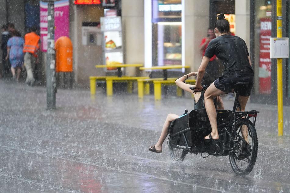 Junge Leute fahren während des Starkregens mit einem Lastenfahrrad die Friedrichstraße entlang. Das Wetter bleibt wechselhaft.