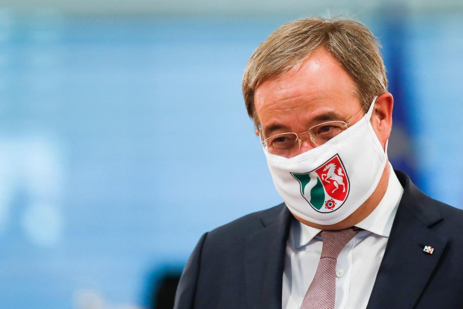 Armin Laschet, Ministerpräsident von Nordrhein-Westfalen, trägt am Mittwoch eine Gesichtsmaske mit dem Wappen von Nordrhein-Westfalen, als er zu einer Gesprächsrunde zwischen Bundeskanzlerin Merkel und Ministerpräsidenten der Bundesländer im Kanzleramt eintrifft.