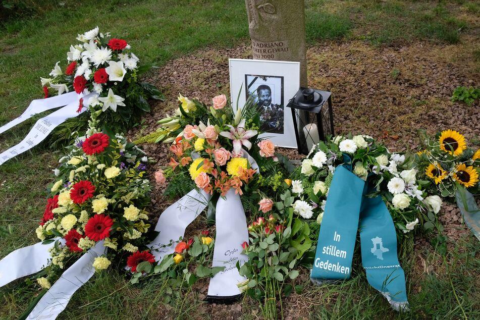 Blumen, Kränze, eine Kerze und ein Foto des ermordeten Alberto Adriano liegen an einem Gedenkstein im Stadtpark von Dessau.