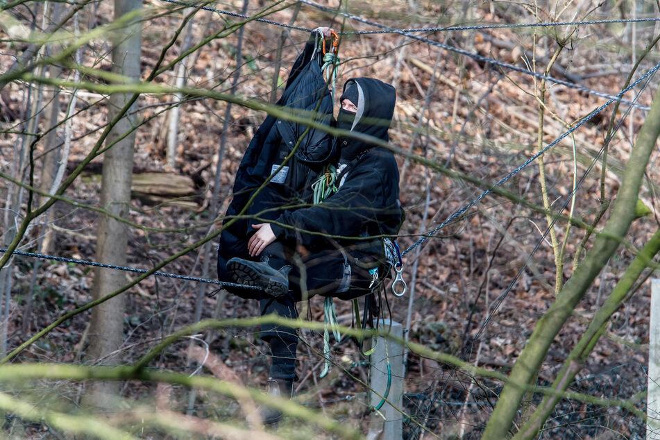 Ein Umweltschützer sitzt auf einem Seil im Bahnhofswald. Polizisten haben mit der Räumung des Waldes begonnen.