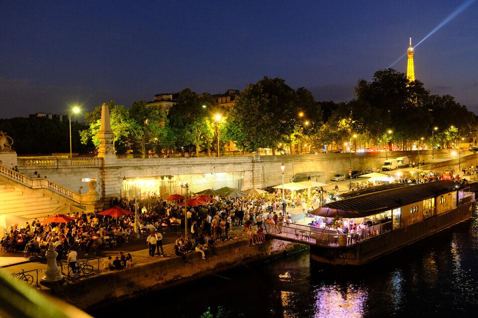 Besucher sitzen am Ufer der Seine und essen und trinken. In Frankreich dürfen Bars und Restaurants ihre Terrassen unter der Einhaltung von Sicherheitsmaßnahmen wieder öffnen.