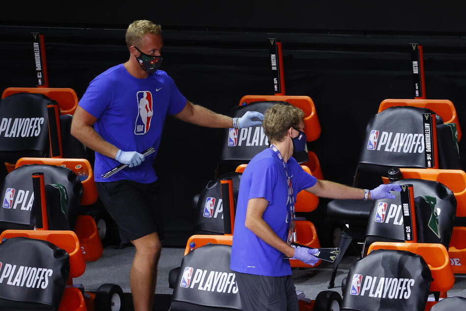 Employees remove cards bearing the players' names from chairs at Amway Center.