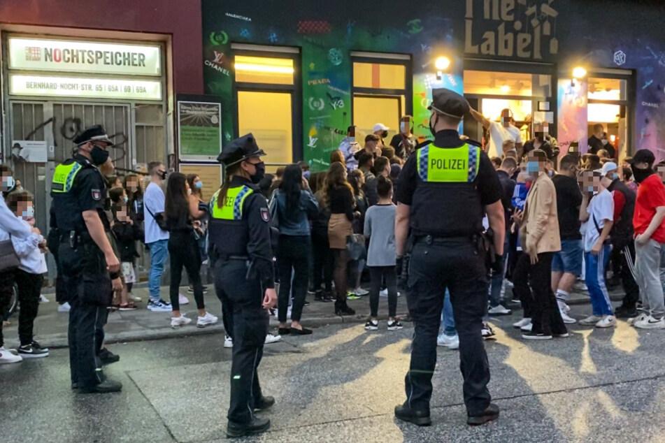 """Die jugendlichen Fans stehen, beobachtet von den Beamten, dicht gedrängt vor dem Laden """"The Label""""."""