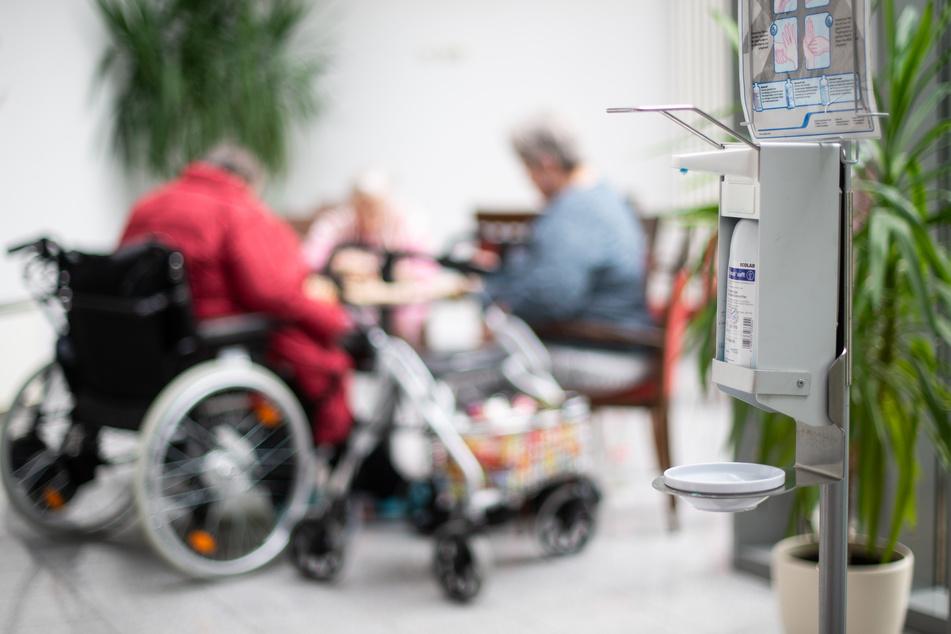 Ein Desinfektionsmittelspender hängt in einem Altenzentrum, während im Hintergrund Seniorinnen spielen.