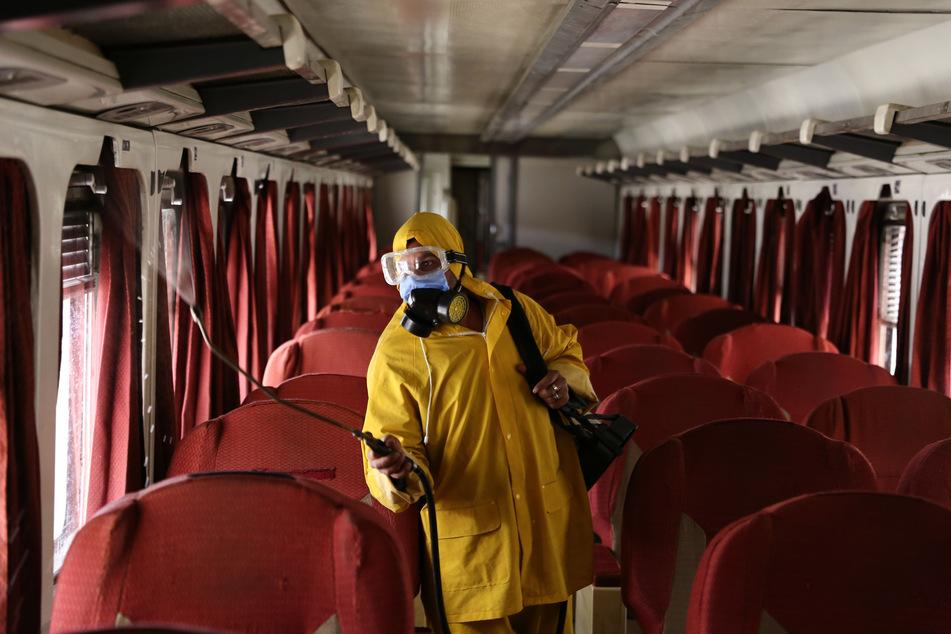 Ein Arbeiter versprüht in einem leeren Zug in Ägypten Desinfektionsmittel.