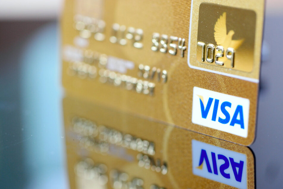 Eine Visa-Kreditkarte spiegelt sich in der Oberfläche eines Tisches.