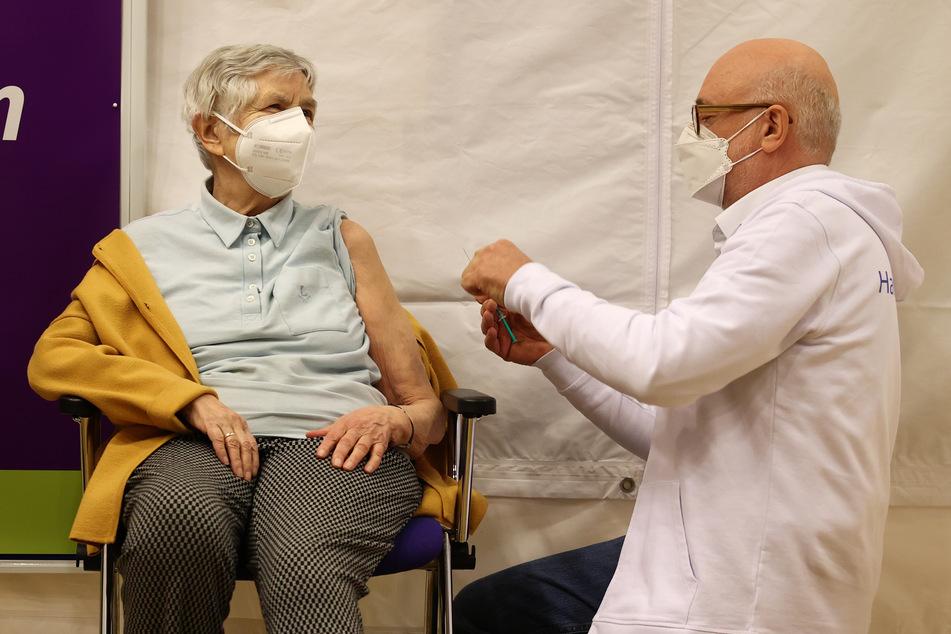 Karin Sievers (84) bekommt von Dirk Heinrich (r.), ärztlicher Leiter des Impfzentrum Hamburg an den Messehallen, die erste Impfung im Hospital zum Heiligen Geist im Stadtteil Poppenbüttel.