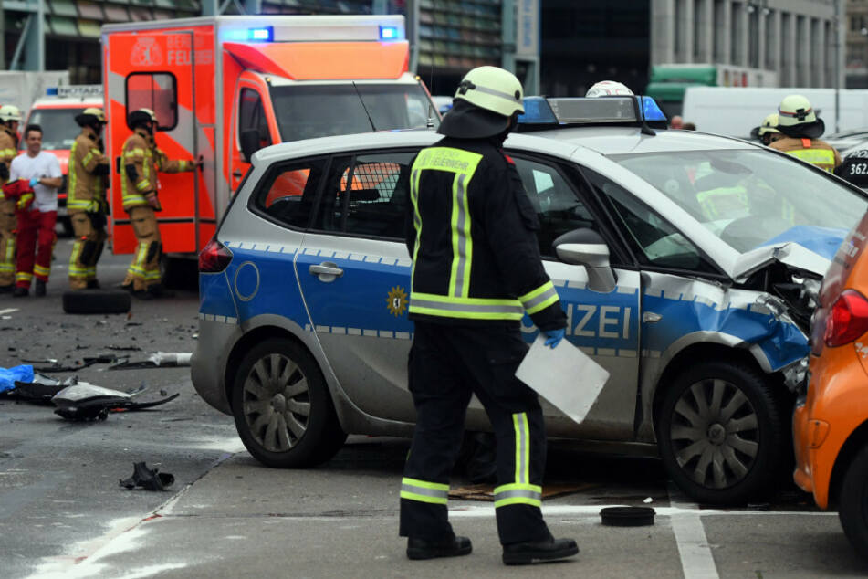 Ein Feuerwehrmann betrachtet das Unfallauto.