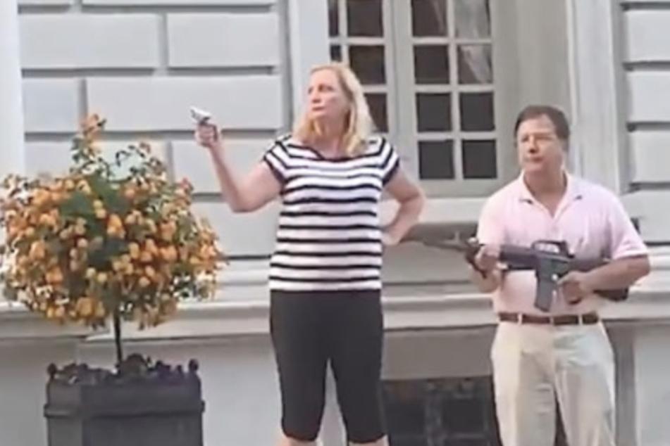 Das Paar bedroht die Protestierenden zunächst von ihrer Terrasse aus mit Waffen.