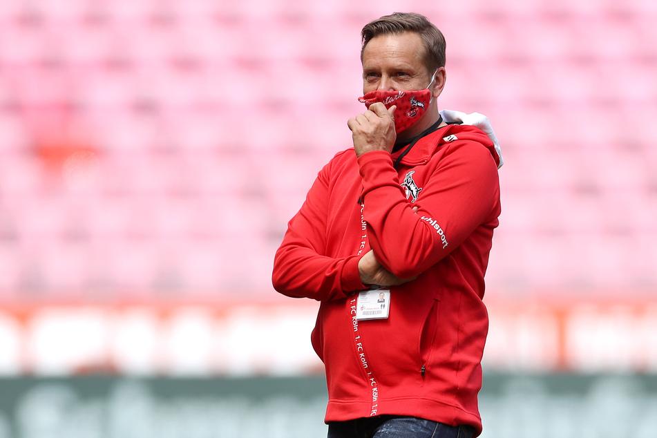 Kölns Sportdirektor Horst Heldt steht mit Maske im Stadion.