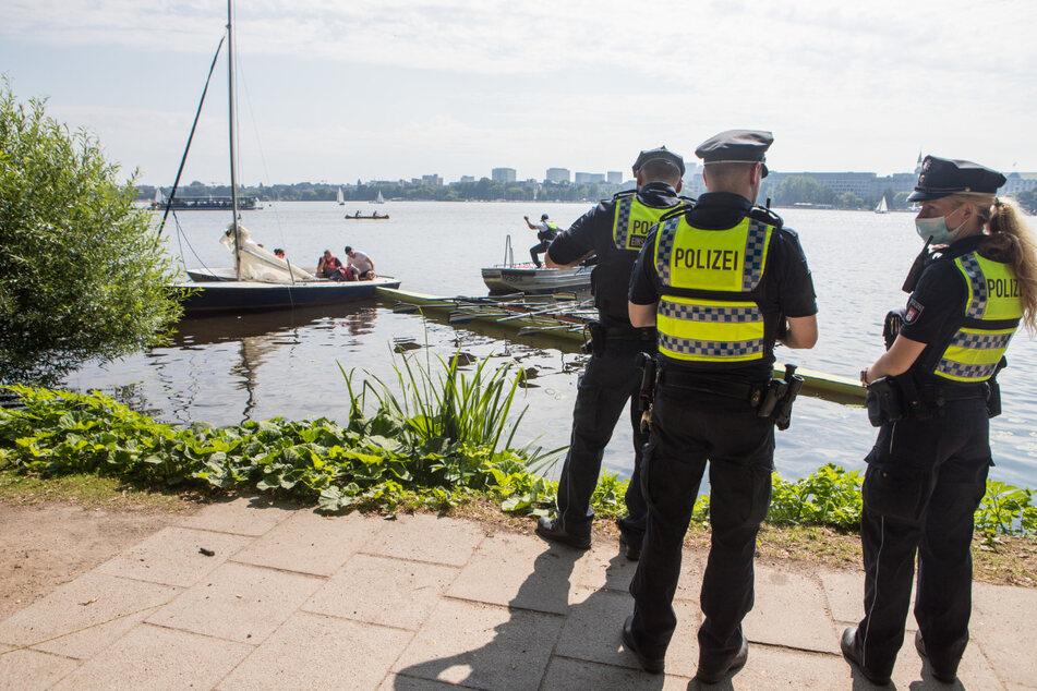 Polizisten stehen an der Alster. Im Hintergrund ist zu sehen, wie das Ruderboot in der Jolle feststeckt.