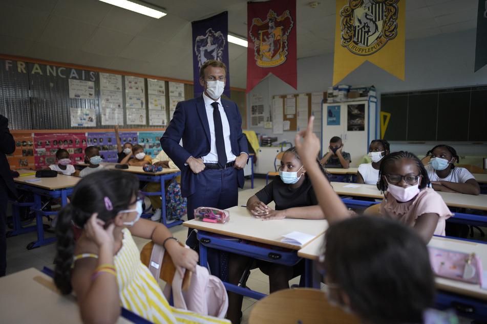 Emmanuel Macron (M), Staatspräsident von Frankreich, steht in einem Klassenzimmer während eines Besuchs der Bouge-Grundschule im Bezirk Malpasse.