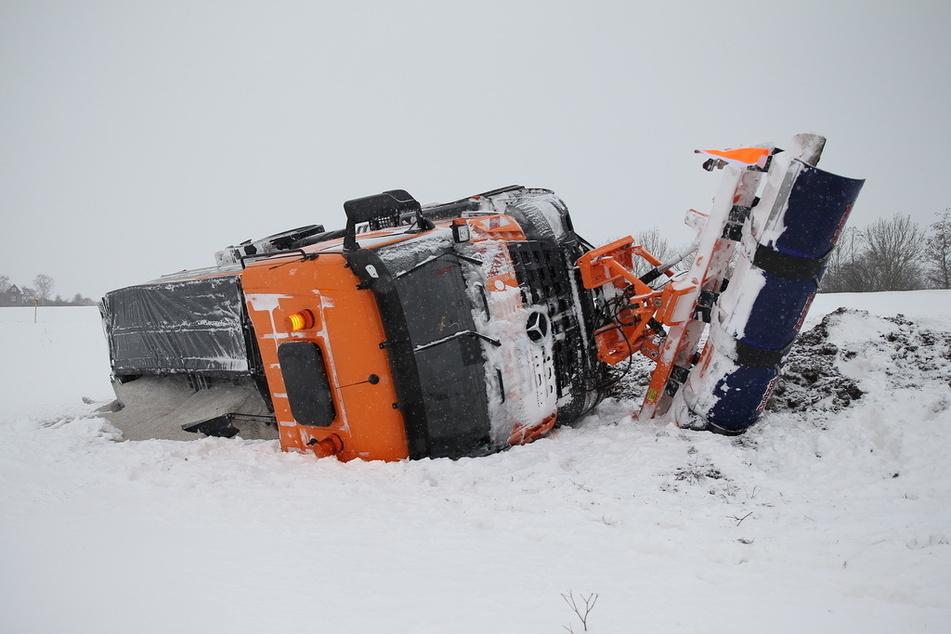 Beim Räumen der schneeverwehten Straße kam dieser Winterdienst von der Fahrbahn ab und kippte um.
