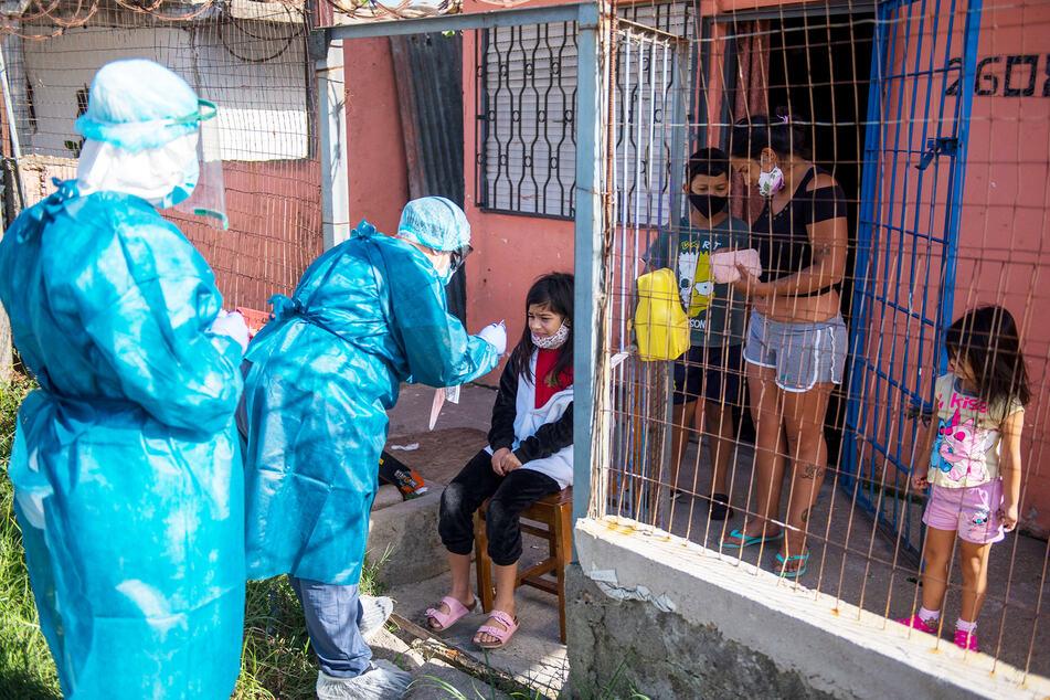 Ein Mitarbeiter des Gesundheitswesens testet ein Kind auf Covid-19. Uruguay steht vor einem starken Anstieg von Corona-Fällen.