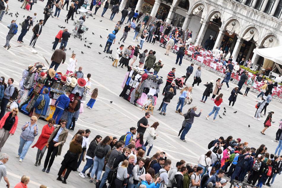 In der Zeit des Pre-Openings der Art Biennale Venedig 2019 spazieren Touristen über den Markusplatz.