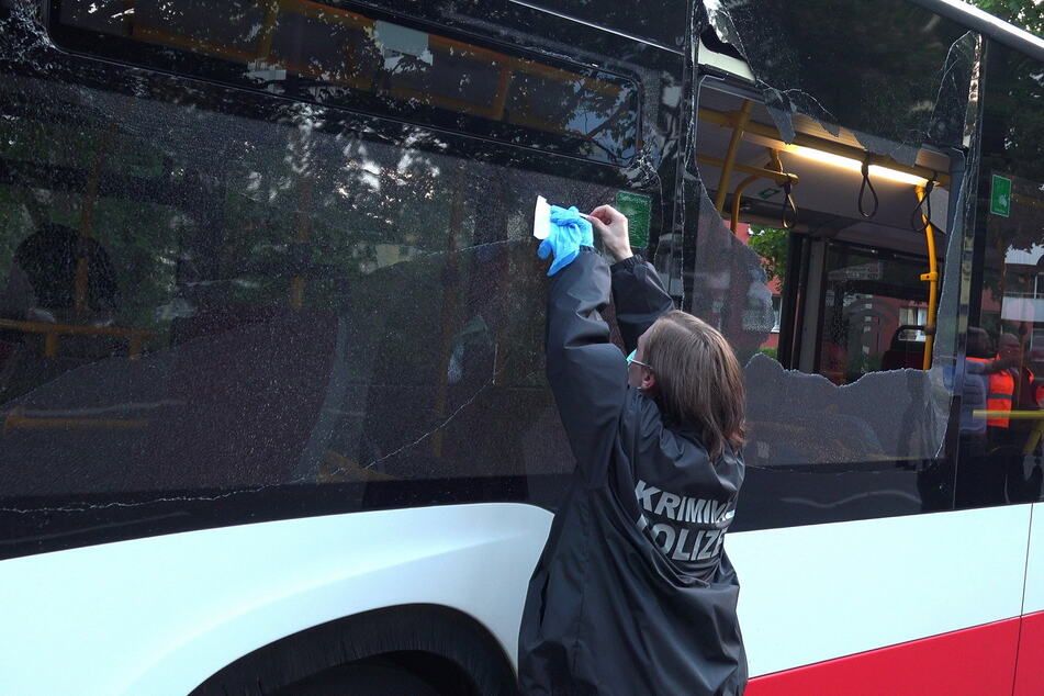 Eine Mitarbeiterin der Kriminalpolizei sichert Spuren an einem der beschossenen Busse.