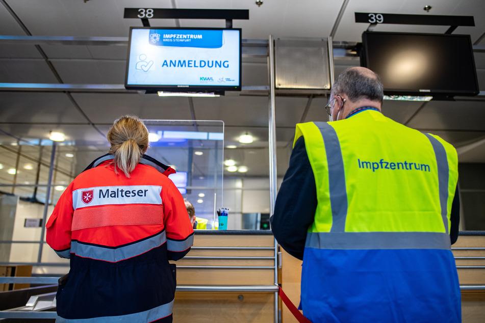 Eine Helferin vom Malteser Hilfsdienst steht an der Anmeldung im Terminal am Flughafen Münster-Osnabrück neben einem Mitarbeiter des Impfzentrums des Kreises Steinfurt.