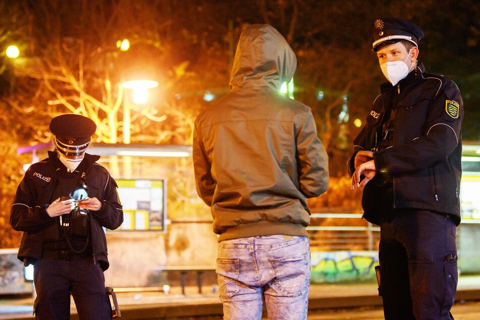 Polizisten überprüfen in der Nacht im Rahmen einer Kontrolle der Ausgangssperre einen Mann. Dies könnte ab sofort wieder häufiger passieren.