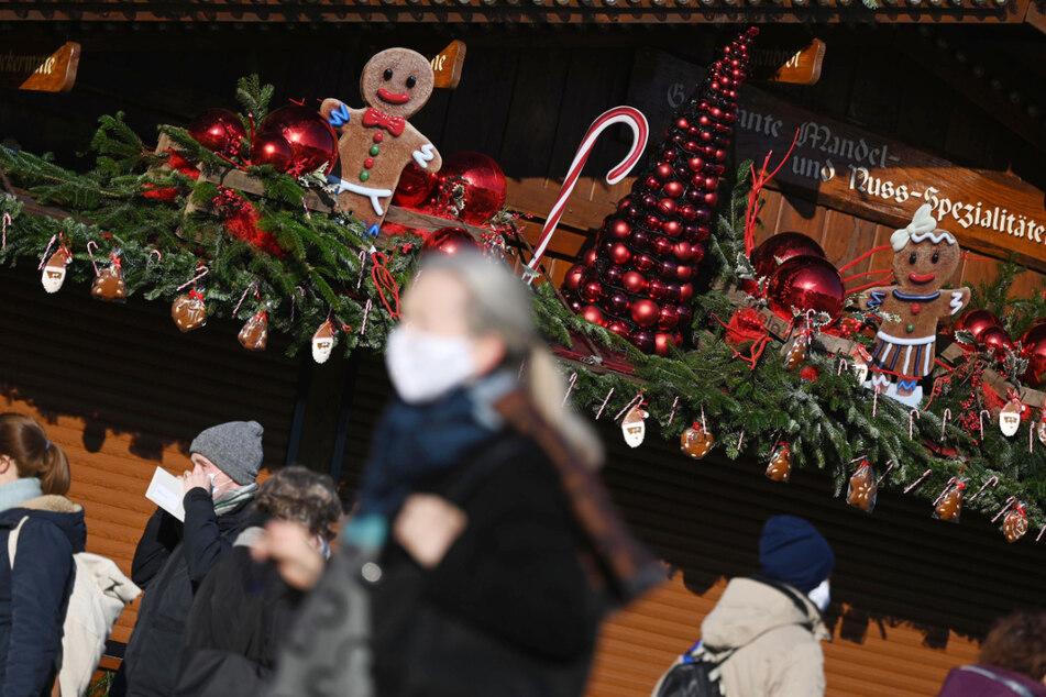 Passanten vor einem weihnachtlich geschmückten Stand in der Stuttgarter Innenstadt.