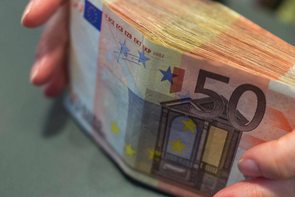 Eine Bank-Mitarbeiterin hält 5000 Euro in 50-Euro-Scheinen in den Händen. In Berlin und Brandenburg sind im ersten Quartal 2021 die Verbraucherpreise stärker als die Einkommen stiegen. (Symbolfoto)