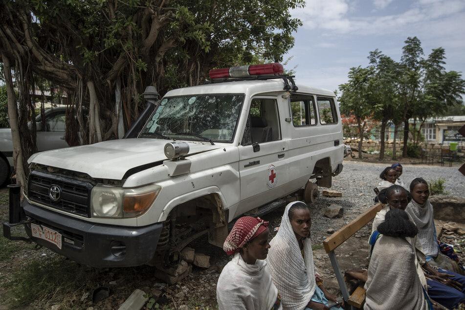 Ein Krankenwagen, der nach Angaben von Anwohnern von eritreischen Soldaten beschädigt wurde, steht neben Menschen, die im Mai 2021 vor einer Klinik in der Region Tigray auf einen Termin warten.