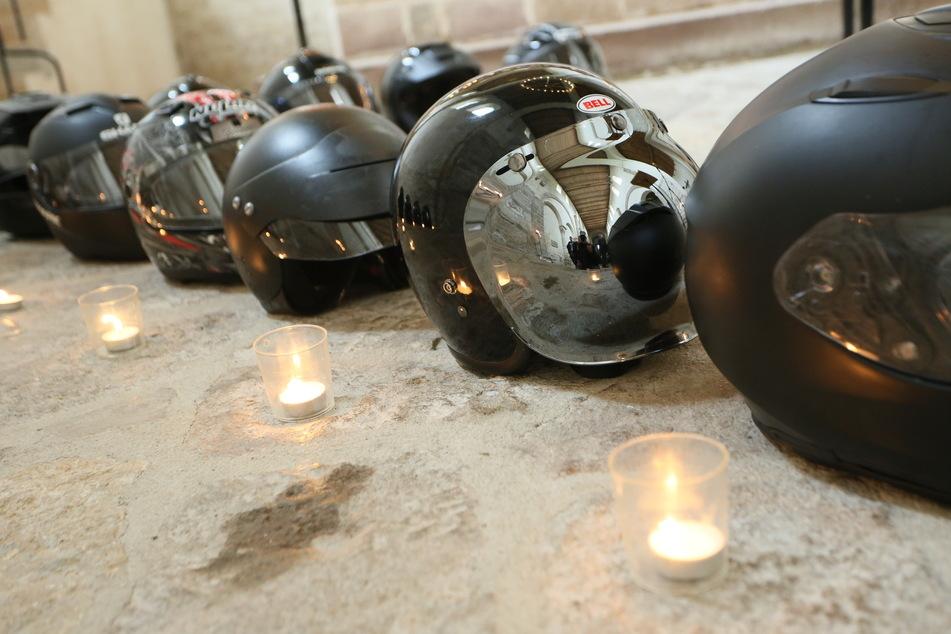In Erinnerung an verstorbene Biker stehen bei einem Biker-Gottesdienst im Harz Kerzen vor Motorradhelmen.