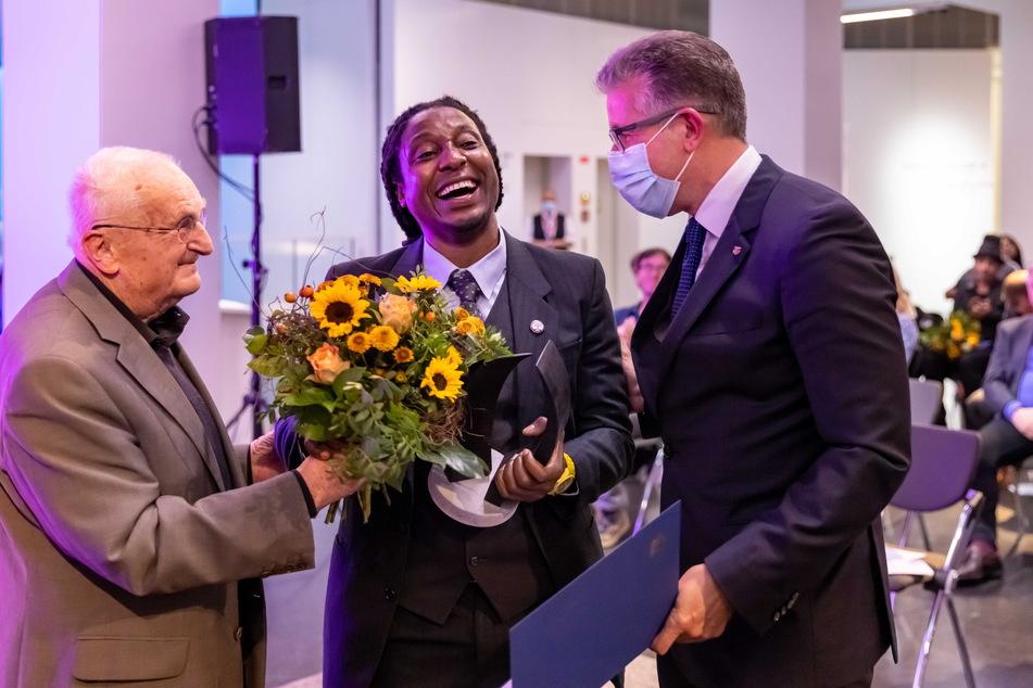 Jurymitglied Hartwig Albiro (89. l.) und Kämmerer Ralph Burghart (50, CDU, r.) überreichten Arba Manillah (42) den Chemnitzer Friedenspreis.