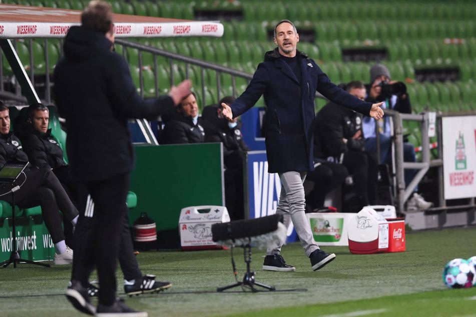 Eintracht Frankfurts Coach Adi Hütter (r.) und Werder-Trainer Florian Kohfeldt diskutieren am Spielfeldrand.