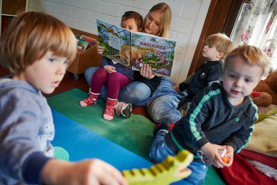 Eine Kita-Erzieherin schaut mit einem Kind in ein Bilderbuch. Eltern und andere einrichtungsfremde Personen müssen eine Maske tragen.