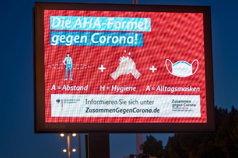 """""""Die AHA-Formel gegen Corona"""" ist auf einem Werbedisplay an einer Straße zu sehen. """"A=Abstand, H-Hygene, A=Alltagsmasken""""."""