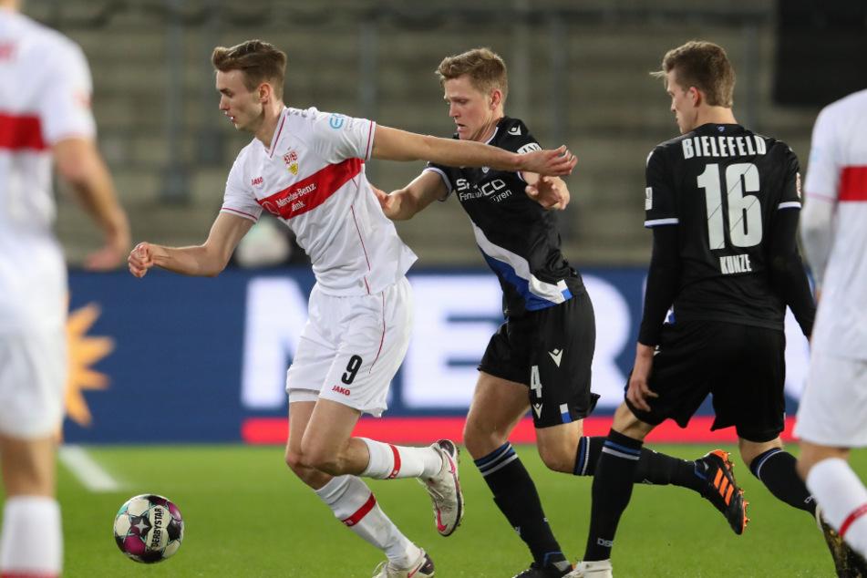 VfB-Stürmer Sasa Kalajdzic (l.) wird von Bielefelds Joakim Nilsson (Mitte) verfolgt.