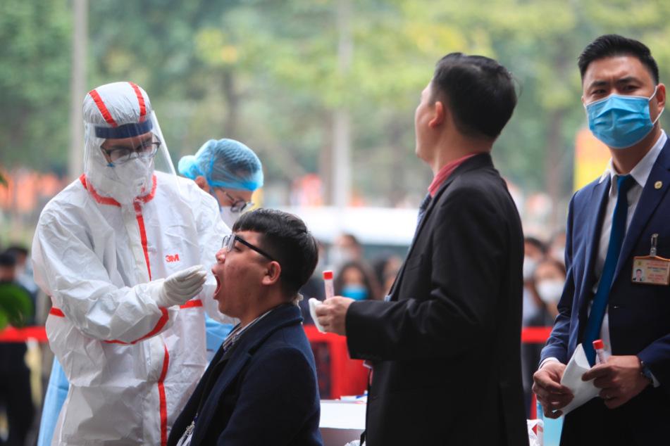 Hanoi: Ein Mitarbeiter des Gesundheitswesens nimmt für einen Corona-Test eine Abstrichprobe von einem Sicherheitsbeamten am Veranstaltungsort des Kongresses der Kommunistischen Partei.