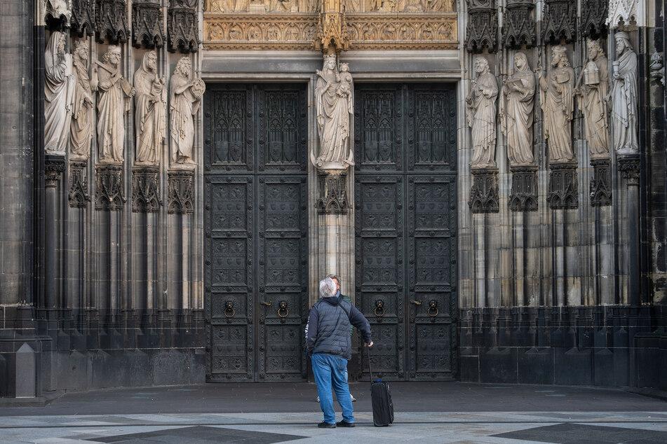 Ein Besucher steht vor den verschlossenen Türen des Kölner Doms