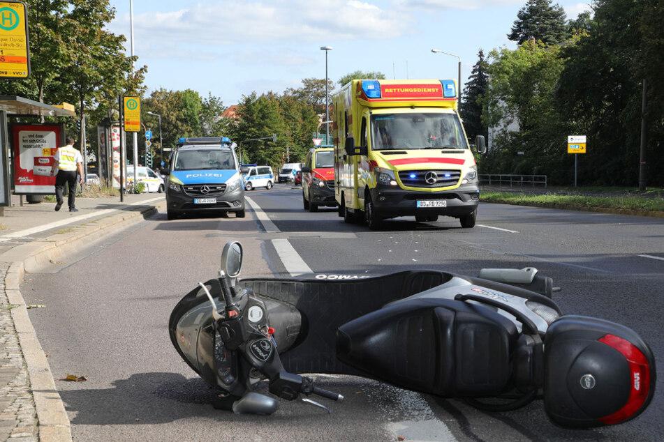 Das Moped liegt auf der Straße, Polizei und Krankenwagen sind im Einsatz.