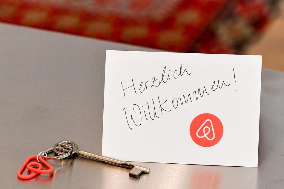 Ein Schlüssel mit einem Airbnb-Anhäger und eine Herzlich-Willkommen-Karte liegen in der Wohnung eines Airbnb-Gastgebers für den Gast bereit.