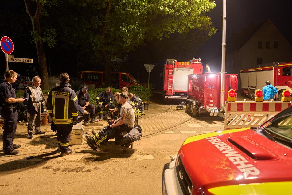 Erschöpfte Feuerwehrleute machen in Bad Neuenahr-Ahrweiler mitten in der Nacht eine Pause.
