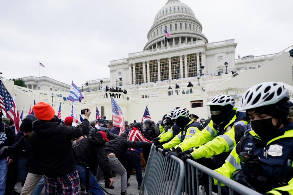 Unterstützer des US-Präsidenten Trump versuchen eine Absperrung vor dem Kapitol zu durchbrechen.