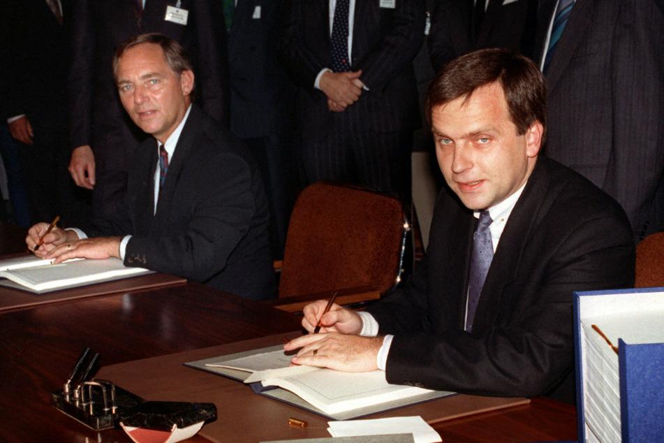 Wolfgang Schäuble (78, l., CDU), damals Bundesinnenminister, und der damalige DDR-Staatssekretär Günther Krause (67) bei der Unterzeichnung der Urkunden zum Einigungsvertrag. (Archivbild)