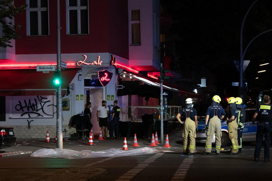 Feuerwehrleute stehen vor der Shisha-Bar in der Müllerstraße in Berlin-Wedding, wo in der Nacht zum 21. Juni knapp 30 Schüsse auf drei Männer abgefeuert wurden.