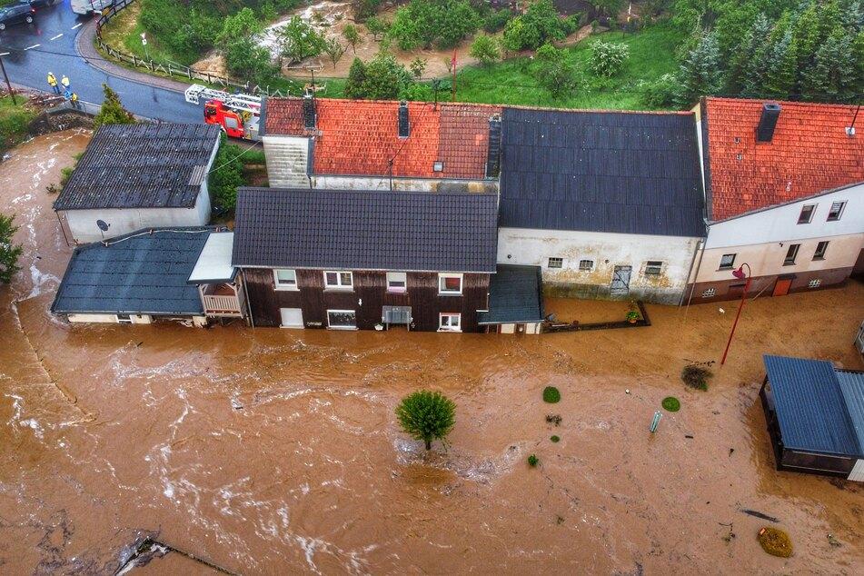 Häuser in Gebroth sind nach dem Unwetter von Hochwasser umgeben. Unwetter haben Einsatzkräften in Rheinland-Pfalz am Samstag viel Arbeit beschert.
