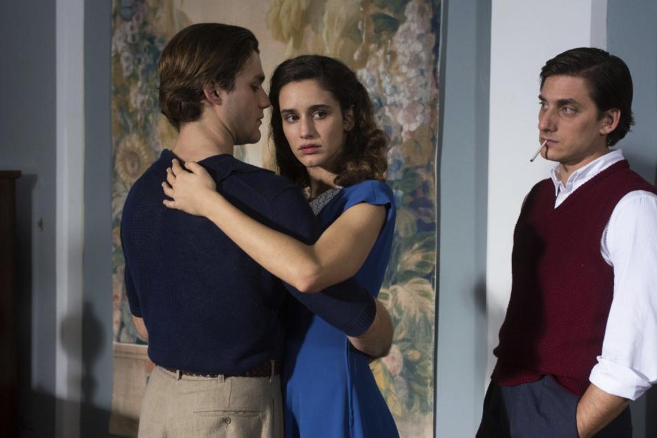 Milton (r., Luca Marinelli) schaut zu, wie Fulvia (Valentina Bellé) eng umschlungen mit Giorgio (Lorenzo Richelmy) tanzt.