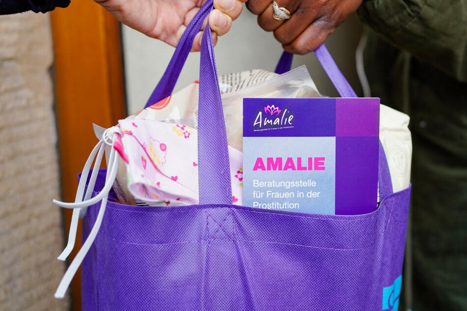 """In Mannheim nimmt eine Prostituierte an einer Haustür eine mit Lebensmitteln und Informationsmaterial gepackte Tasche der Beratungsstelle """"Amalie"""" entgegen."""