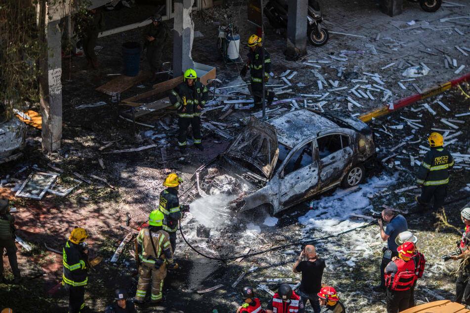 Im israelischen Ramat Gan arbeiten Feuerwehrleute an einem Autowrack vor einem Wohnhaus, das im Mai 2021 von einer Rakete der islamistischen Hamas getroffen wurde. Zwei Monate nach den Raketenangriffen auf Israel kommen 60 israelische Kinder und Jugendliche zur Erholung nach Berlin.