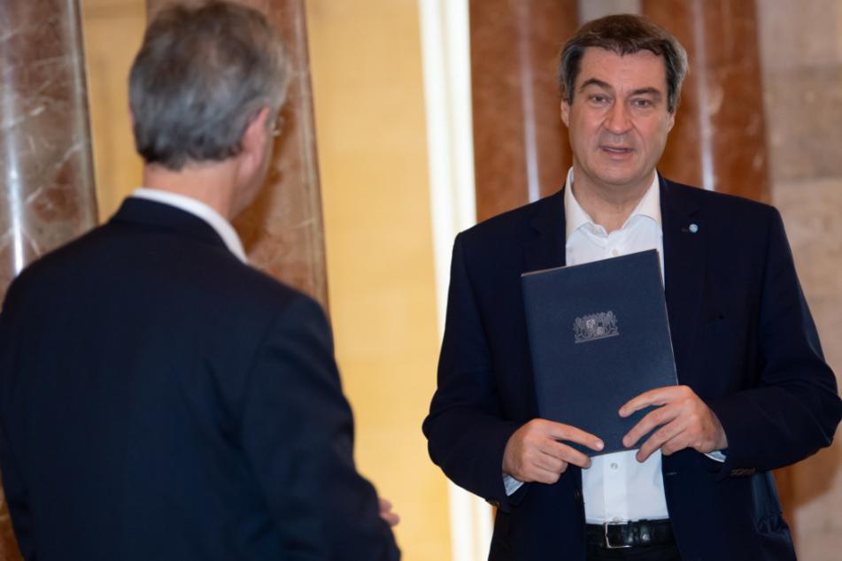 Markus Söder (r, CSU), Ministerpräsident von Bayern, und Michael Piazolo (Freie Wähler), Kultusminister von Bayern, unterhalten sich vor Beginn einer Sitzung des bayerischen Kabinetts.
