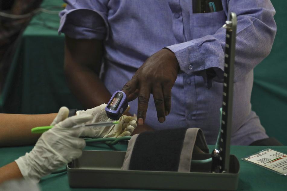 Ein Arzt in Indien überprüft die Vitaldaten eines Mannes, bevor er ihm einen Corona-Impfstoff im Government Fever Hospital verabreicht. Bei der weltweiten Auslieferung der Corona-Impfstoffe kommt es wegen Exportbeschränkungen in Indien zu deutlichen Verzögerungen.