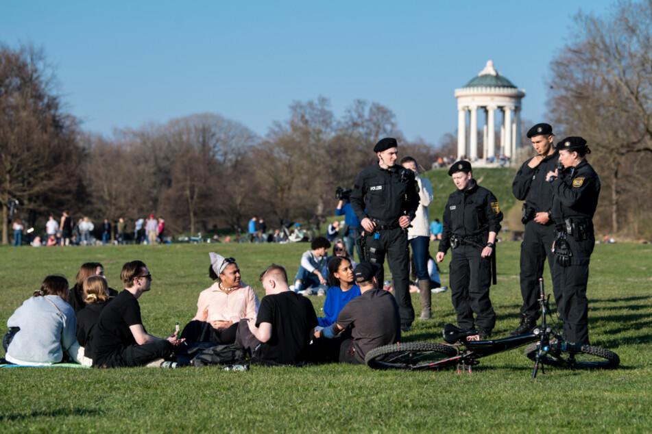 Polizisten reden im Englischen Garten mit einer Gruppe Jugendlicher.