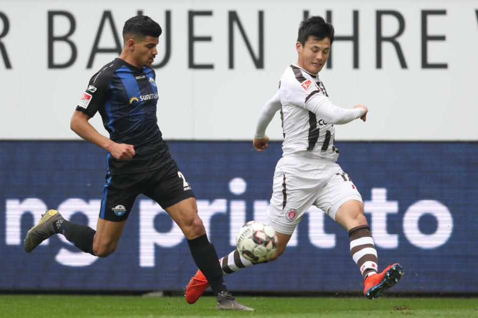 Paderborns Mohamed Dräger (links, SC Paderborn 07) im Kampf um den Ball mit Ryo Miyaichi aus Hamburg.