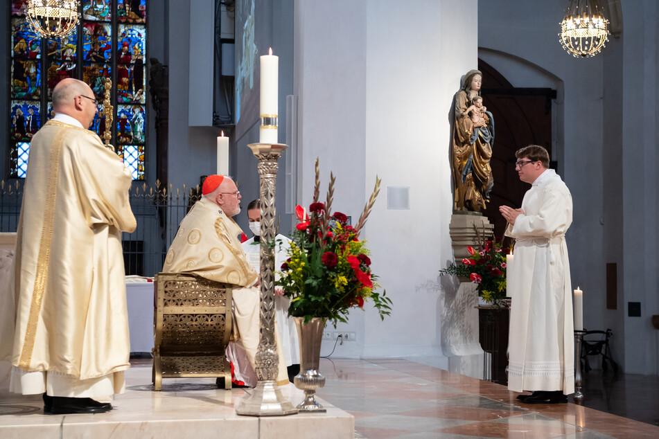 Kardinal Reinhard Marx (M), Erzbischof von München und Freising, und der Priesteranwärter Robert Daiser (r) nehmen im Liebfrauendom an einem Gottesdienst teil. Während des Gottesdienstes wurden fünf Priesteranwärter zu Diakonen geweiht.